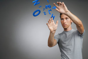 Young man in t-shirt working with a set of letters on grey background, writing concept.